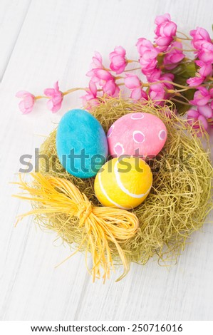 Pretty and Colorful Easter Eggs in Nest Still Life with Bright Pink Flowers on Rustic Weathered White Board Background from above, looking down view.  Closeup horizontal - stock photo