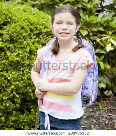 Pretty and happy little girl with backpack - stock photo