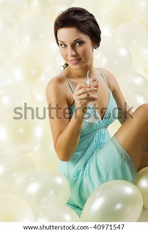 pretty and young brunette with a glass of champagne sitting between balloons - stock photo