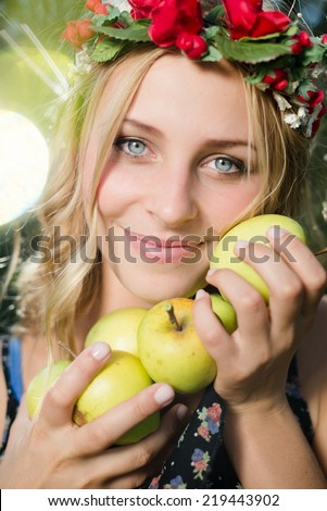 pretty apple fairy: young woman cute blond girl smiling among red apples with wreath of flowers & sun light flares of rays looking at camera on summer outdoor copy space background - stock photo