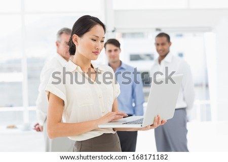 Pretty asian businesswoman using laptop with team behind her in the office - stock photo