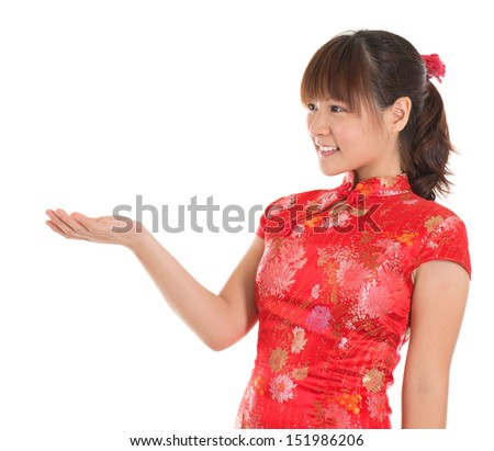 Pretty Asian female with Chinese traditional dress cheongsam or qipao hand showing blank space. Chinese new year concept, female model isolated on white background. - stock photo