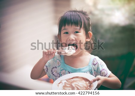 Pretty asian girl eating ice cream in the summer on blurred background. Happy child looking at camera. Outdoors. Vintage style. - stock photo