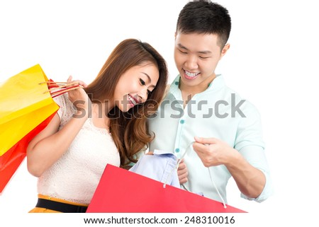 Pretty Asian girl looking at the shopping bag of her boyfriend - stock photo
