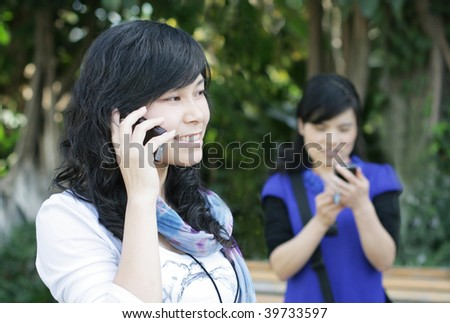 Pretty Asian girl using a cell phone