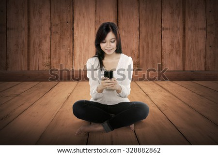 Pretty asian girl using cellphone on the wooden floor. Telecommunication concept - stock photo