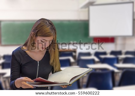 Pretty Asian middle school student reads book in classroom