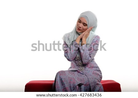 Pretty asian muslim woman wearing traditional malay costume known as songket is making sleeping sign with her hands while sitting on red sofa on white background  - stock photo