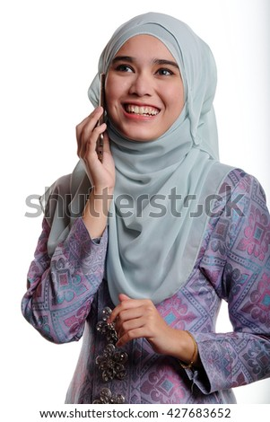 Pretty asian muslim woman wearing traditional malay costume known as songket is smiling and laughing while talking on her mobile phone on white background  - stock photo
