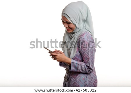 Pretty asian muslim woman wearing traditional malay costume known as songket is smiling while texting her mobile phone on white background  - stock photo