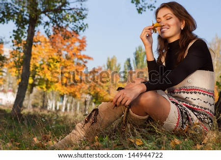 Pretty asian woman relaxing at the autumn park - stock photo