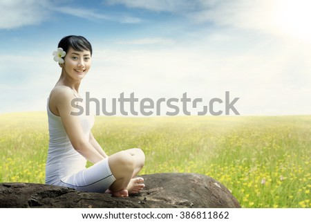 Pretty Asian woman sitting on the rock while meditating and smiling at the camera, shot on the meadow at springtime