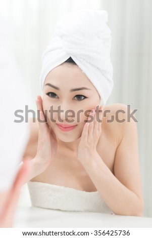 Pretty Asian woman washing face in bathroom