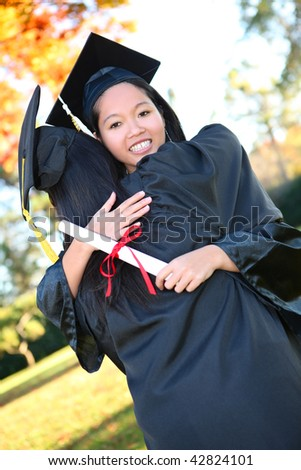 Pretty Asian woman wearing cap and gown holding diploma at graduation hugging friend - stock photo