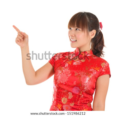 Pretty Asian woman with Chinese traditional dress cheongsam or qipao finger pointing at blank copy space. Chinese new year concept, female model isolated on white background. - stock photo
