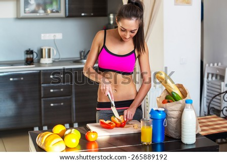 Pretty attractive athletic active sportive lady woman standing in kitchen with a towel on her shoulder and healthy food fresh fruits milk bread. - stock photo