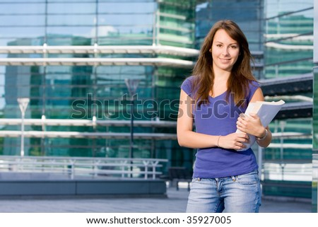 Pretty attractive caucasian white girl standing outside modern college school with books