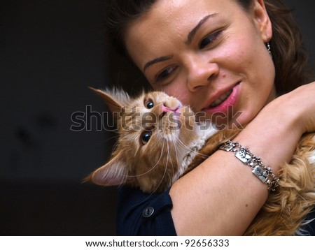 Pretty attractive young woman with a cat play together at home - stock photo