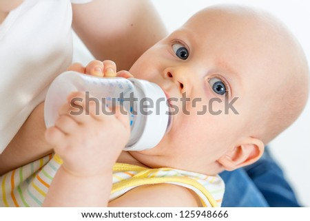 Pretty baby boy drinking milk or water from bottle - stock photo