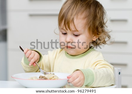 Pretty baby eating with plug - stock photo