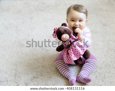 Pretty baby girl bites the paw of the toy bear - stock photo