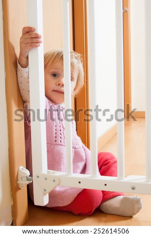 Pretty baby sitting at safety gate of  stairs - stock photo