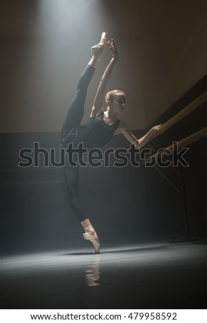 Pretty ballerina makes a pose under the falling light. She is outstretching her legs and one arm. One hand she puts on the barre. Low key photo.