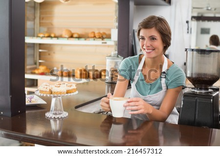 Pretty barista offering cup of coffee smiling at the coffee shop - stock photo