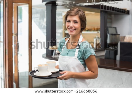 Pretty barista smiling at camera holding tray at the coffee shop - stock photo