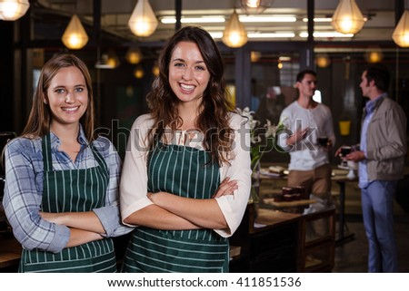 Pretty baristas standing with arms crossed in the bar
