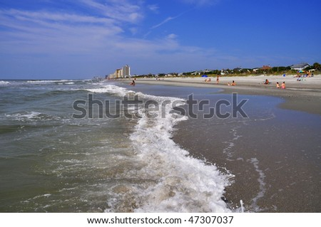 pretty beach scene with surf - stock photo
