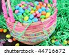 Pretty beaded Easter basket full of colorful Easter candies on a rustic wooden table. - stock photo