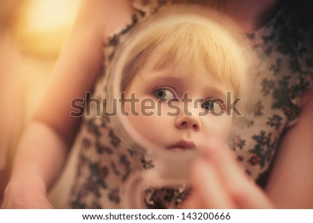 Pretty beautiful girl looks in the mirror - stock photo