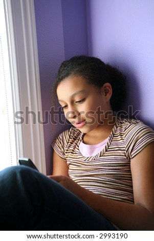 pretty biracial girl looking at her cell phone - stock photo