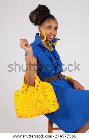 Pretty black woman in a blue dress and yellow purse, looking at the camera thoughtfully  - stock photo