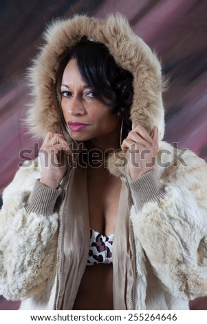 Pretty Black woman in a fur coat with a hood covering her head - stock photo