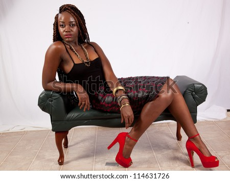 Pretty black woman in black blouse, sitting and relaxing while looking left with a friendly but serious expression - stock photo