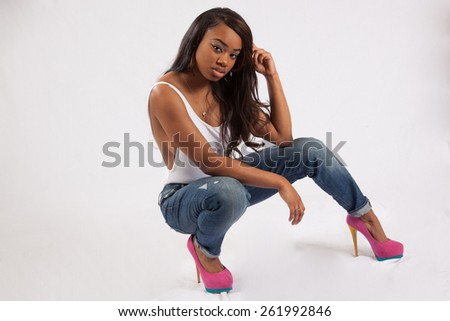 Pretty black woman in blue jeans and white shirt,  looking thoughtfully at the camera  - stock photo