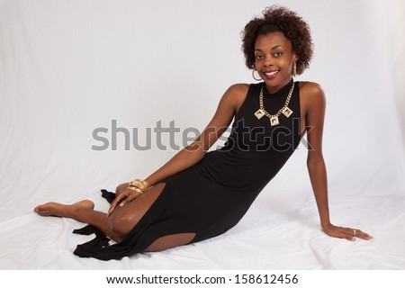 pretty black woman in shorts  sitting on a wooden stool and smiling at the camera
