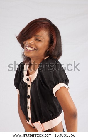 Pretty black woman pulling her blouse up a little to show her thin abdomen in a flirting way,