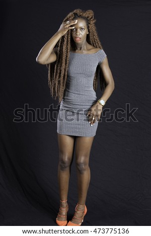 Pretty Black woman with long dreadlocks,  looking as if she has a headache