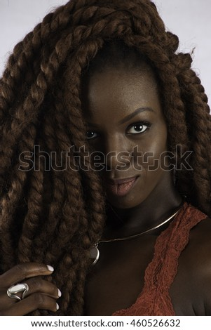 Pretty black woman with long dreadlocks looking   at the camera with a smile - stock photo