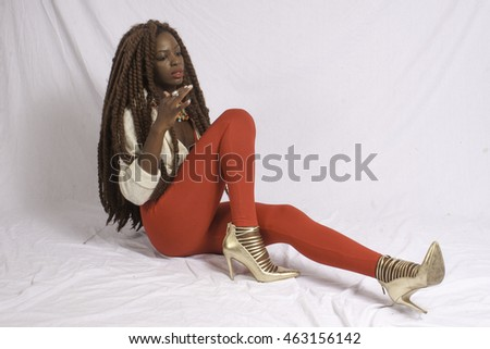 Pretty black woman with long dreadlocks looking thoughtful