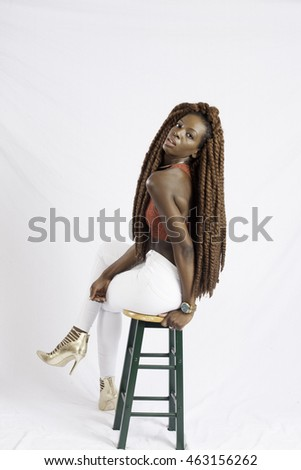 Pretty black woman with long dreadlocks looking thoughtfully at the camera