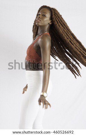 Pretty black woman with long dreadlocks looking thoughtfully at the camera and slinging her hair - stock photo