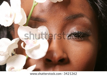 Pretty black woman with orchid - stock photo