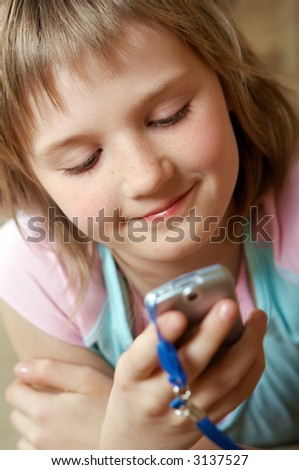 Pretty blond caucasian teenager reading a message.Youth lifestyle. - stock photo