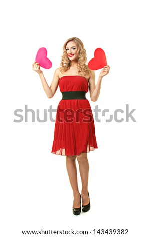 Pretty blond girl in red dress make choice between two hearts - stock photo