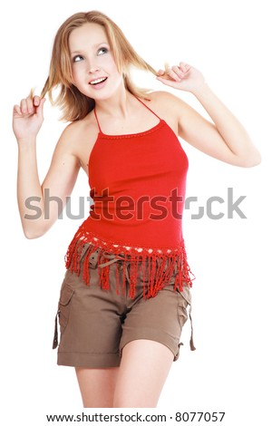 Pretty blond girl in red top and shorts dancing with dreamy smile