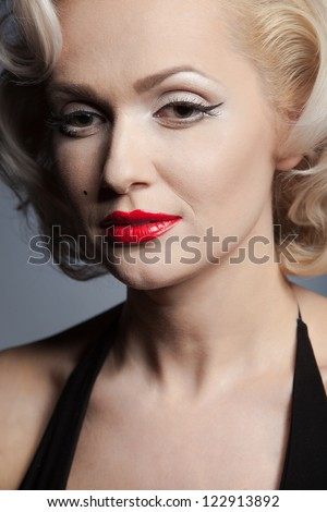 Pretty blond girl model like Marilyn Monroe in black dress with red lips on gray background - stock photo